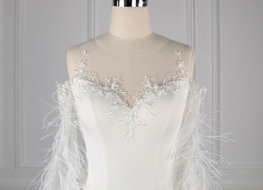 robe de mariée moulante épaule découvert col illusion manches longues plumés